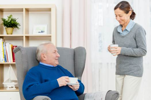 Carer and man having coffee in home