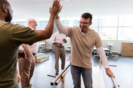 Man doing rehab giving high five to support worker