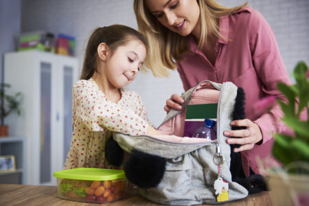 Mother and daughter packing school bag