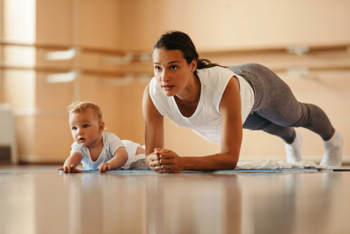 Lady exercising with child sitting next to her